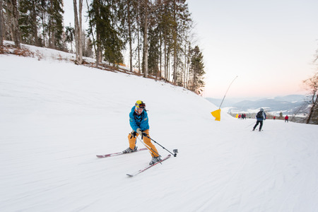 Guy on skis riding down the mountain slope and taking selfie with stick on the winter resort Stock Photo