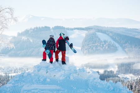 Couple of snowboarders enjoy the snow-white scenery of mountains and forests of the Carpathians from the height of the mountain top at winter ski resort on a beautiful sunny day. Back view Banco de Imagens