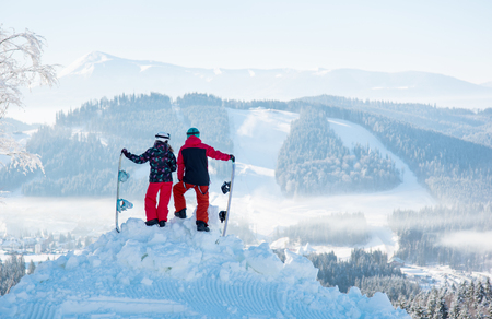 Two snowboarders enjoy the snow-white scenery of mountains and forests of the Carpathians from the height of the mountain top on a beautiful sunny winter day. Back view