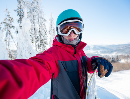 Shot of a young man snowboarder taking a selfie, wearing helmet, skiing mask and colorful winter snowboarding clothing, standing on top of the mountain Stock Photo