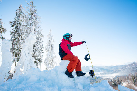 Man snowboarder sitting on top of a snowy hill with his snowboard enjoying stunning mountains view ski resort copyspace seasonal activity. Ski season and winter sports concept Stock Photo