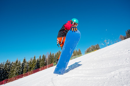Low angle shot of a male snowboarder jumping while skiing on the slope in the mountains on a beautiful sunny winter day active lifestyle sports concept
