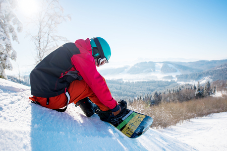 Male snowboarder in winter sportswear helmet and skiing mask sitting on the slope preparing for riding copyspace active lifestyle winter sports recreation resort