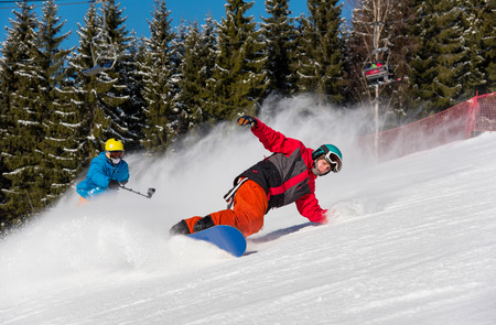 Male snowboarder skiing on the snowy slope and professional skier cameraman shooting him by action camera on monopod at ski resort on a sunny winter day. lifestyle activity recreation concept