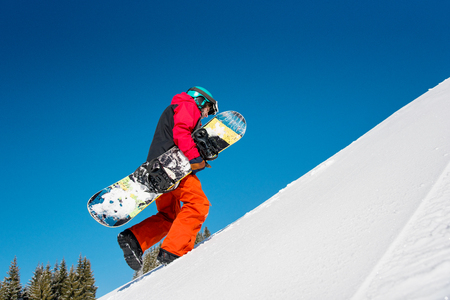 Full length shot of a fully equipped snowboarder freerider walking up the slope carrying his snowboard on sunny day in the mountains copyspace nature outdoors winter sport active lifestyle concept