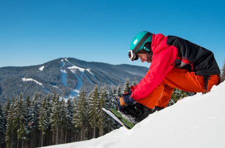 Shot of a snowboarder sitting on the snowy slope, preparing for riding downhill on a beautiful sunny winter day. Blue sky, mountains, forests, ski slopes on the background. copyspace sports concept
