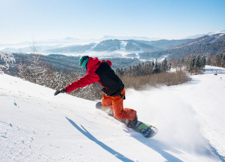 Rearview shot of a freerider snowboarder riding down on the snowy slope at winter ski resort in the mountains copyspace recreation adrenaline extreme lifestyle Stock Photo