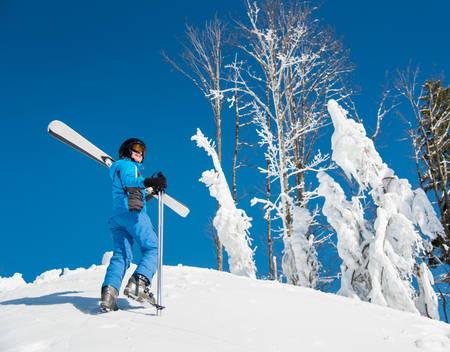 Shot of a female skier enjoying stunning view of snowy mountains while walking up the slope carrying her skis. Blue sky and forest on the background copyspace