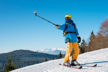 Shot of a professional skier taking a selfie using selfie stick posing on the slope copyspace recreation active sport seasonal resort sportspeople adrenaline extreme concept Фото со стока