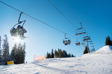 Low angle shot of a ski-lift in the mountains on a sunny winter day copyspace people riding top nature extreme activity sport recreation concept ski resort