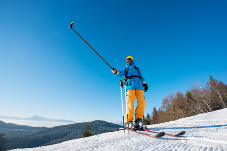 Professional skier standing on top of a mountain on a beautiful sunny winter day taking a selfie with action camera on selfie stick at the winter resort copyspace modern technologies memories concept