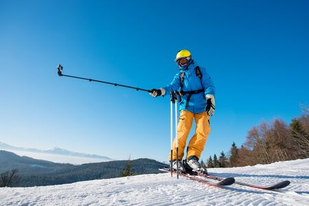 Full length shot of a skier standing on top of a mountain on a beautiful sunny winter day taking a selfie with action camera on monopod. Blue sky and winter forest on the background