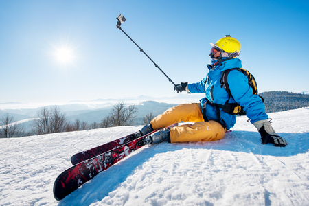 Skier sitting on the ski slope taking a selfie using selfie-stick resting relaxing extreme recreation lifestyle activity technology concept. Blue sky with sun and winter forest on the background