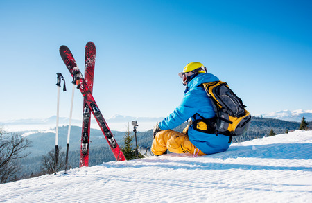 Rearview shot of a skier sitting on top of the mountain near his skiing equipment relaxing enjoying beautiful snowy mountains view people living enjoyment recreation travelling riding Archivio Fotografico