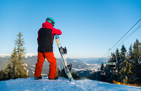 Rear view shot of a snowboarder standing with his snowboard, observing nature at ski resort on a beautiful sunny winter evening copyspace active lifestyle winter sports Bukovel Ukraine