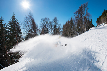Skier taking selfies photo with a camera on monopod while skiing on fresh powder snow in the mountains. Blue sky, sun and winter forest on the background. active lifestyle sport technology action Stock Photo