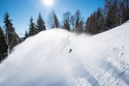 Action shot of skier taking selfies with a camera on selfie stick while skiing on fresh powder snow in the mountains active lifestyle sport winter technology youth movement. Focus on the camera