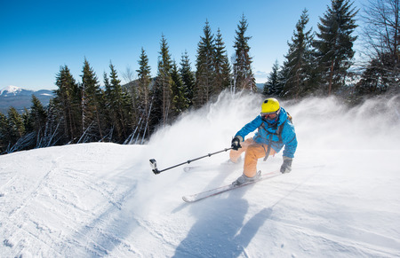 Action shot of professional skier taking selfies photo with a camera on selfie stick while skiing on fresh powder snow in the mountains at the winter resort Bukovel active lifestyle sport concept