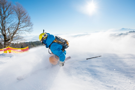 Rearview shot of a freerider skier sliding down the slope at ski resort mountains copyspace ski resort recreation travelling tourism vacation extreme adrenaline