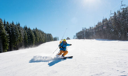 Professional skier riding down the hill enjoying skiing in the mountains outdoors sport recreation extreme lifestyle people travelling resort concept Stock Photo