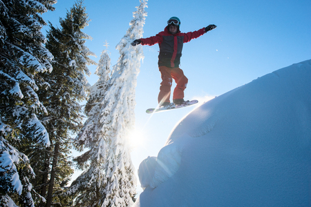 Freerider snowboarder jumping in the air while riding on the slope in the mountains. Blue sky and sun on the background. Ski season and winter sports concept