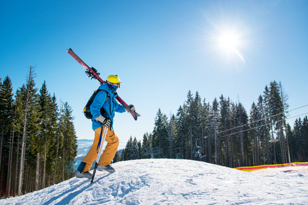 Shot of a male skier walking up the slope in the mountains carrying his gear on his shoulder on a sunny day at winter resort copyspace active lifestyle equipment skiing concept Stock Photo