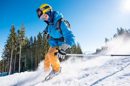 Male skier skiing on fresh snow in the mountains on a sunny beautiful day extreme fun happiness activity lifestyle concept