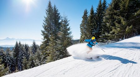 Skier riding downhill in the mountains copyspace sports recreation winter ski resort people lifestyle active activity adrenaline equipment concept