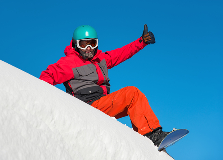 Full length shot of a happy snowboarder sitting in the snow on top of the mountain, smiling and showing thumbs up to the camera. Blue sky on the background
