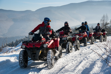 Group of people driving off-road quad bikes on snow at top of the mountain in winter Stock Photo