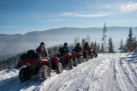 Group of people driving off-road quad bikes in the winter mountains Stock Photo