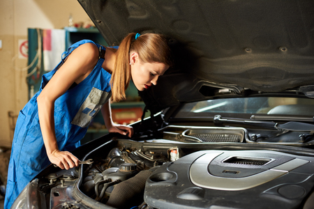 Young girl in a blue suit tries to repair the car and looks under its hood. 版權商用圖片 - 92653758