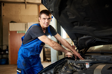 Close-up of mechanic in a dirty work uniform repairs a car in his repair shop. The bonnet is open, the guy looks at the camera Reklamní fotografie