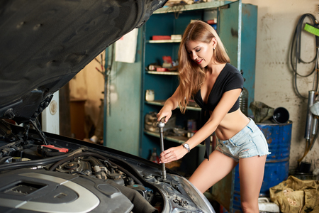 A young woman mechanic poses while using wrench to tighten the bolts 스톡 콘텐츠