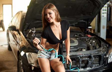 A girl sits on the car hood and smiles to the camera with an automatic screwdriver in her hands.
