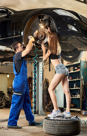The car on the hydraulic lift guy and girl is being inspected him. The guy is dressed in a blue work uniform. Girl in short shorts and T-shirt stands on the tire