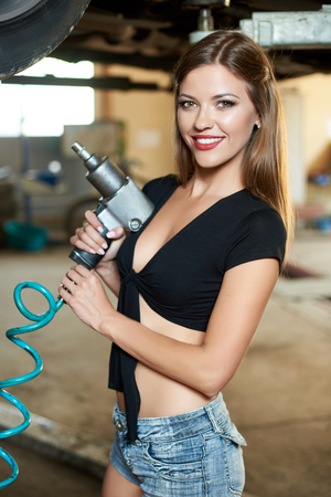 Smiling female mechanic is posing with an automatic screwdriver in her hands