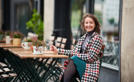 Outdoor portrait of a young attractive brunette woman is sitting at terrace in a cafe on the street of Budapest. Woman looks at the camera with a smile, her hair is developed by the autumn wind