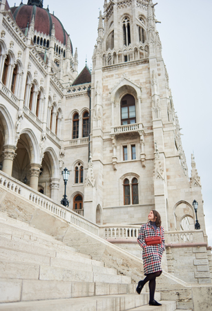 Female walking down the steps of the parliament of Budapest looked back to enjoy a large-scale architectural structure. Stylishly dressed in red tones. 스톡 콘텐츠