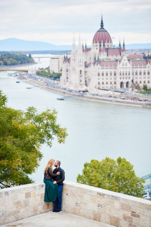 Lovers couple gently touching each other on the background of Danube River and Parliament Building in Budapest, Hungary.