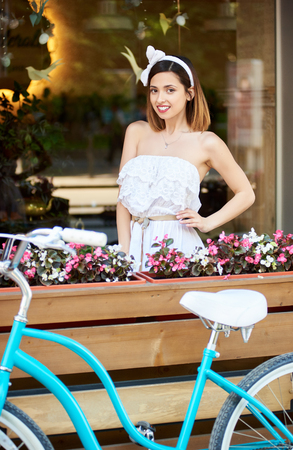 Pretty brunette girl in white posing next to cosy cafe decorated with flowers next to her blue bike on sunny summer day. Beautiful girl photoset photoshoot smiling happy life model turquoise bicycle. Stock Photo