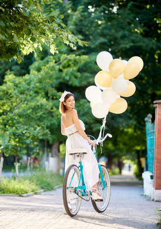 Pretty young female in long white dress looking back while riding vintage blue bike decorated with colorful balloons down green park alley on sunny summer day. Beautiful girl smiling happy posing