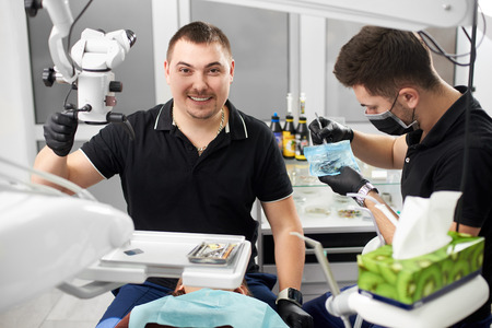 Male dentist with ceramic braces is smiling to the camera while another is working with medical instruments Фото со стока
