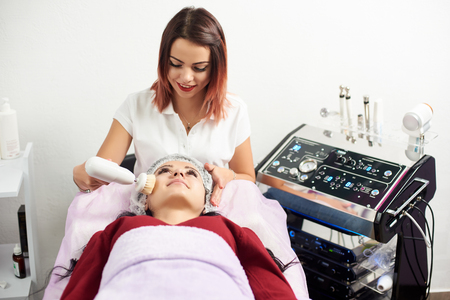 Cosmetologist makes the apparatus a procedure of Hardware face cleaning with a soft rotating brush of a beautiful, young woman in a beauty salon.