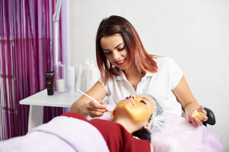 Beautiful female cosmetologist is smiling while applying gold mask to a face of a brunette client in a fashionable beauty salon.