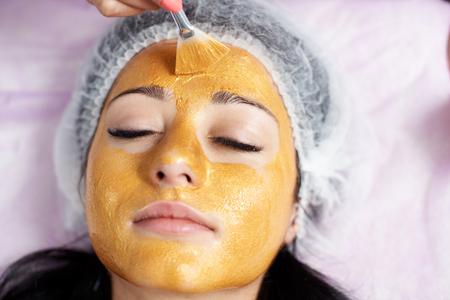 Primer plano de la cara de una clienta de un salón de belleza con una máscara de oro. Cosmetología y rutina de cuidado de la piel.
