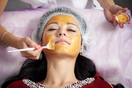 Young woman in a special hat on her head applying gold facial mask. Hardware cosmetology. Close-up Stock Photo