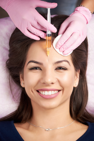 Smiling woman getting injection for female forehead face in the cosmetology salon. Doctor in medical gloves and mask with syringe injects cheeks drug. Close-up Stock Photo