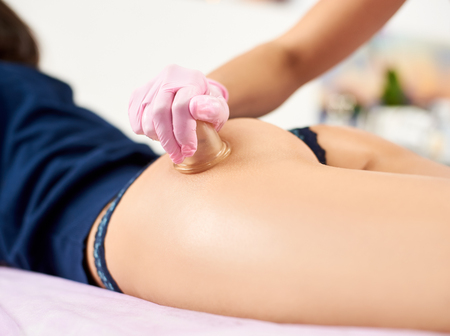 Closeup of a cupping-glass massage performed by a professional in pink gloves to a toned female client of a salon.