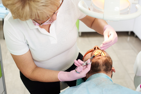 Dentist woman makes anesthetizing injection within a patients mouth. Injection techniques to anesthetize the tooth in the modern dental clinic Stockfoto